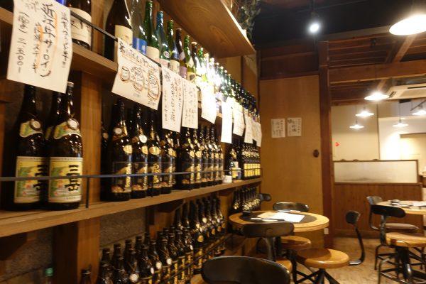 魚丸は日本酒が豊富なお店。壁には日本酒の瓶がずらっと並びます。